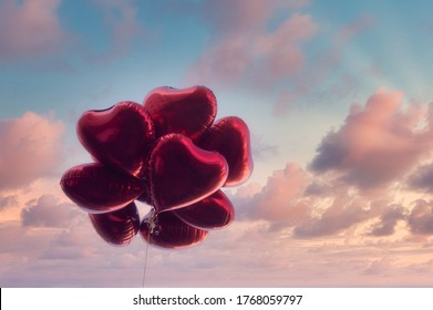 Group of heart shaped red air baloon on dramatic sky with pink clouds. Valentine's day and romance concept.