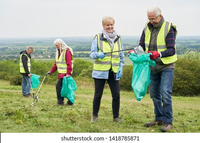 Group Of Helpful Seniors Collecting Litter In Countryside