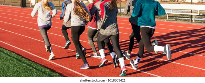 A group of high school girls running away from the camera while doing a workout on the track on a cool winters afternoon.