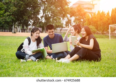 Group of high school students in park and looking at tablet.summer, communication, technology , education and teenage concept