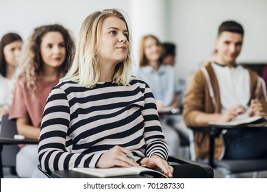 Group of high school students sitting at classroom and following lecture.