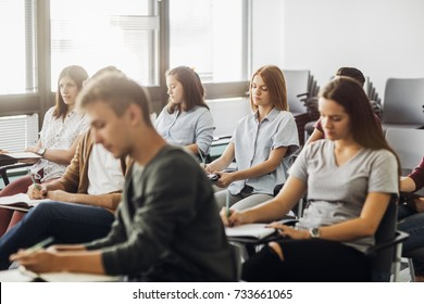 Group of high school students sitting in classroom and writing in notebooks.