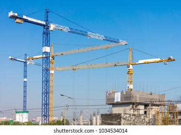 Group of high tower cranes in workplace. Building construction industrial in Thailand, Southeast Asia.