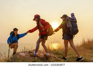 Group Hiker team woman helping her friend climb up the last section of sunset in mountains. Traveler teamwork and family relax walking in outdoor lifestyle adventure and camping. Travel summer life