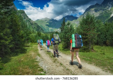 Group of hikers with backpacks climb up to the high mountains. Caucasus, Georgia, Svaneti region.