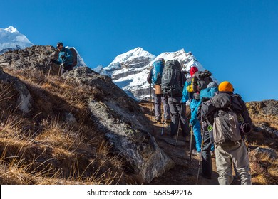 Group of Hikers with Backpacks and high Altitude climbing Gear walking up on steep Footpath towards snowy Summit