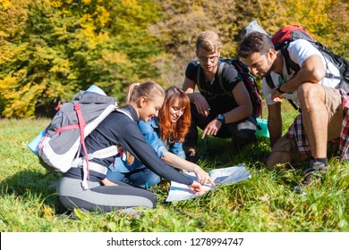 Group of hikers with backpacks looking at map and planning further trekking trail