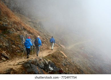 Group hikers with backpacks walking down on mountain trail enjoying on view of foggy mountains. Travel and adventure summer holiday concept