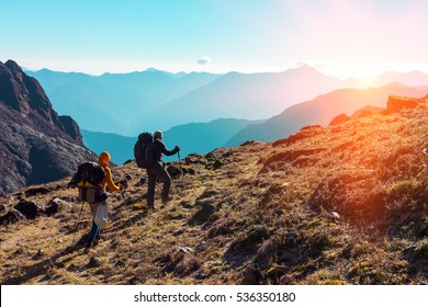 Group of Hikers with Backpacks and walking Sticks walking on grassy Trail towards rising Sun. Layered Mountains View and clean Sky on sunny Background