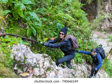 Group of hikers climbing on safety cable on mountain wall