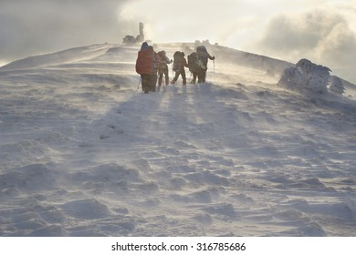 group of hikers climbing in the snowy mountains