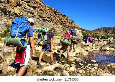 Group of hikers crosses small river in mountains. Shot in the Langeberge highlands near Grootrivier and Gouritsrivier rivers crossing, Garden Route, Western Cape, South Africa.