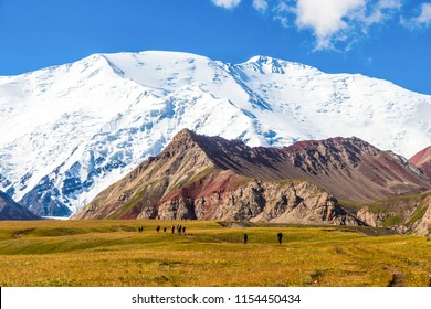 A group of hikers on a meadow at 3000m above sea level with Pik Lenin as a backdrop in Kyrgyzstan