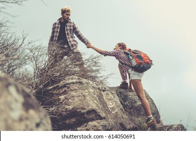 Group of hikers on a mountain. Man helping his friend to climb a rock. Young people on mountain hike. Vintage style.