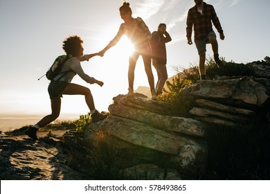 Group of hikers on a mountain. Woman helping her friend to climb a rock. Young people on mountain hike at sunset. - Shutterstock ID 578493865