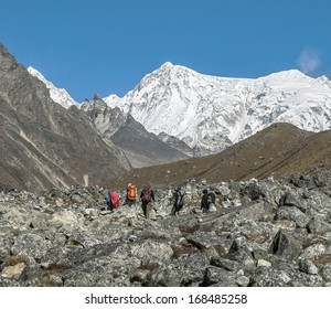 A group of hikers on the trail to the ridge Mahalangur Himal near Cho Oyu with peak Palung Ri (7012 m) in the background - Gokyo region, Nepal, Himalayas
