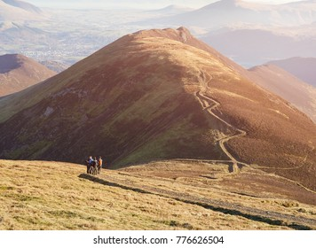 A group of hikers on the winding path up to the summit of Sail and Scar Crags in the distance in the English Lake District, UK.