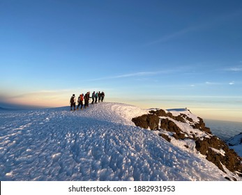Group of hikers reaching the top of Kilimandjaro at sunrise with clear blue sky and walking on snow