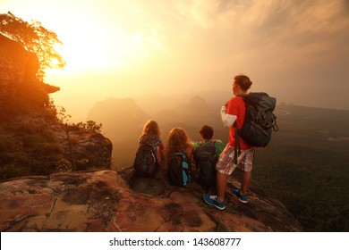 Group of hikers relaxing on top of a mountain and enjoying sunrise