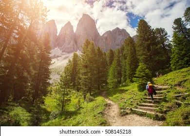 Group of Hikers walking on a mountain trail in vall di Funes, Dolomite Alps, Northern Italy