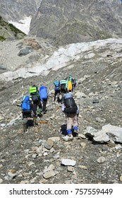 A group of hiking tourists go along the glacier to the mountain pass. The weather facilitates complex movement in the high-mountainous area. Travelling in the Caucasian Mountains in Georgia