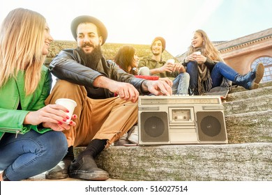 Group of hipster friends drinking cappuccino and listening music outdoor in city center - Young students chilling on free university day - Relaxation concept - Warm filter with focus on bearded man