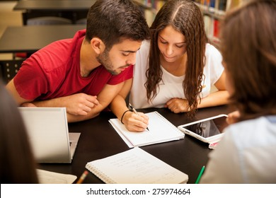 Group of Hispanic students doing homework together in the school library