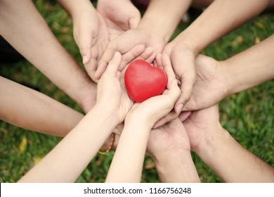 The group of holding hand to protect the red heart as the collaboration of team member in organizations, teamwork and synergy to complete the mission concept.