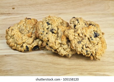 A group of homemade oatmeal raisin cookies on a wooden cutting board.