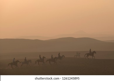 Group of horsemen riding in the desert at sunset