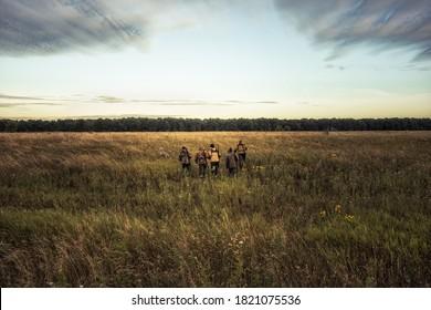 Groupe de chasseurs qui traversent un champ rural vers la forêt contre le soleil levant et la forêt à l'horizon pendant la saison de chasse