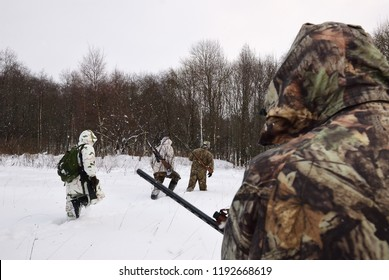 Group of hunters in winter forest with carbines and shotgun at dawn