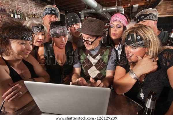 Group of impressed biker gang members watching nerd using a computer