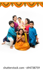 Group of Indian Kids holding Ganpati Idol on Ganesh festival or Chaturthi, welcoming god. Standing isolated over white background
