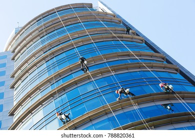 Group of industrial alpinists working on large windows of skyscraper