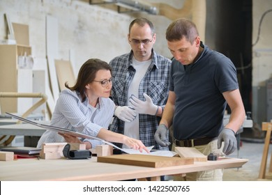 Group of industrial people client, designer or engineer and workers working together on project of wooden furniture. Teamwork in carpentry workshop.