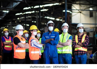 Group of industrial worker team consist of Technicians, Engineer, factory Manager wearing helmet and surgical mask to protect Coronavirus, Covid-19 inflection and safety working in manufacturing plant