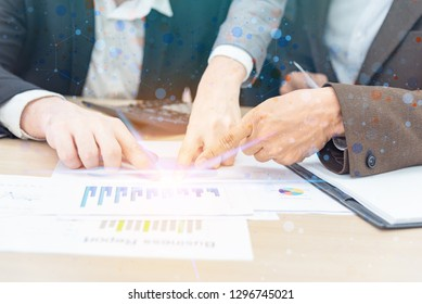 Group of intelligent businessman brainstroming financial figures denoting the progress and pointing turnover graph showing the results for team on desk in office.Business adviser group support concept