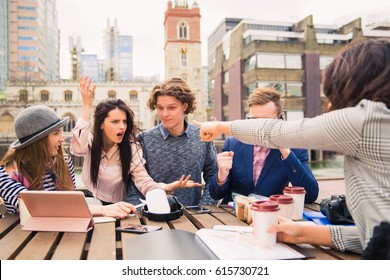 Group of interesting people sit and discuss about something, one of them speaks the phone in time of a break, outdoors