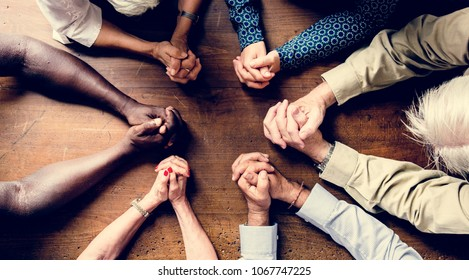 Group of interlocked fingers praying together