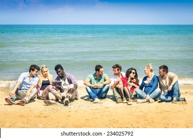 Group of international best friends sitting at beach talking with each other - Concept of multi cultural friendship against racism - Interaction with new technologies tablet and contact with nature