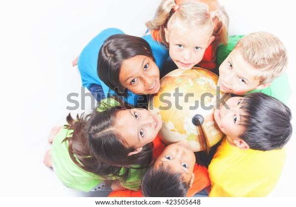 地球儀を持ち、カメラを見上げる国際的な幸せな子どもたちのグループ。学校の子どもは地理を学ぶ。多民族。世界。生態学。純土。国際子どもデー