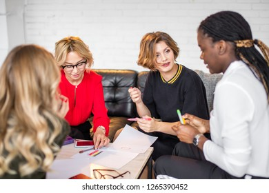 Group of international MLM partners discuss their work in co-working space talking and smiling while sitting at the desk table with smartphones and drawings on paper.