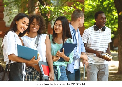 Group of international students resting in campus outdoors during break in classes, chatting and smiling