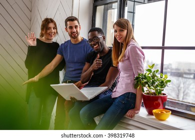 Group of international students using laptop.