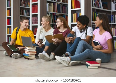 Group of international tennage friends making homework and smiling, library interior, free space