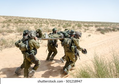 Group of Israeli elite unit combat soldiers carrying a wounded friend on a stretcher through a sandy terrain after a fierce battle against terrorists.