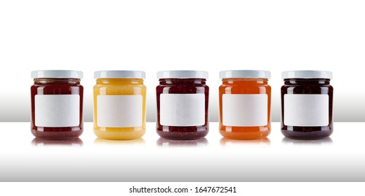 A group jars containing jams and preserves, including rasperry, strawberry, marmalade, chutney and relish, with blank white labels on a white table like surface, with a white background