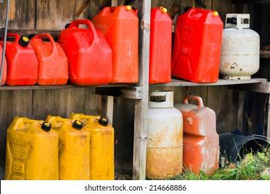 A group of jerry cans and propane tanks sit on shelves in a wooden shed.
