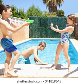 Group of joyful children playing by swimming pool in a home garden on a sunny summer holiday, having fun with water pistols outdoors. Active kids lifestyle, playing in house exterior on vacation.